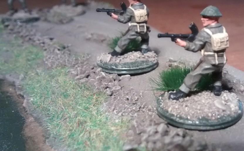 Die beiden MG-Schützen des Trupps tragen das Bren Mk I, ein englisches leichtes Maschinengewehr. Seitlich des Weges tritt der Damm des Weges aus dem dunkelgrünen, morastigen Wasser heraus.