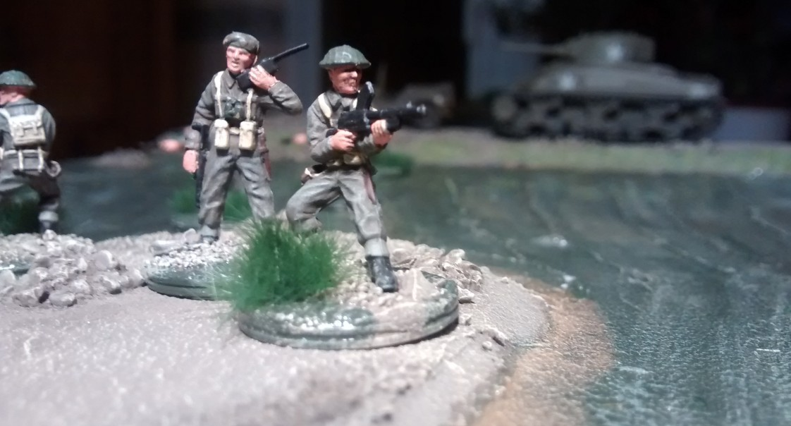 Funker und MG-Schützen nochmals in Nahaufnahme. Das Wasser umspielt die aufragende Erdscholle. Der Wind treibt das Wasser vor sich her und lässt die Oberfläche kräuseln.