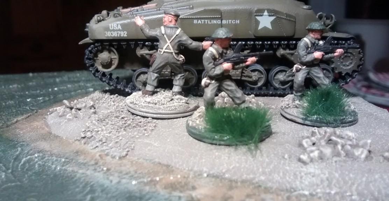 Die MG-Schützen haben nachgezogen. Auf der aus dem Flutgebiet aufragenden Erdscholle versammelt der Offizier seinen Mannen. Der Sherman-Panzer wird das Vorgehen decken.