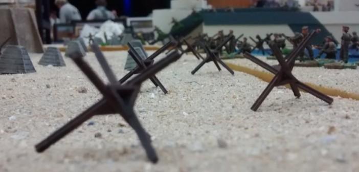 """Das Start-Setting für ein Table-Top-Spiel """"Behind-Omaha"""" auf der Dioramenplatte sieht vier 10er-Trupps der kanadischen 3. Infanteriedivision am Strand vor. Darüber hinaus stehen an Deck des LCI(L) weitere fünf 10er-Trupps zum Anlanden bereit."""