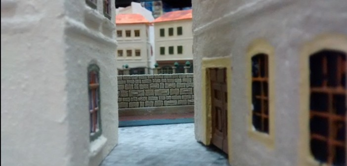 """Blick zwischen den Häusern der Vorstadt hindurch auf den """"Jardin des Roses"""", den Rosengarten der Stadt. """"Behind-Omaha"""" als Spielsystem eignet sich vorzüglich zum Bespielen der Dioramenplatte."""