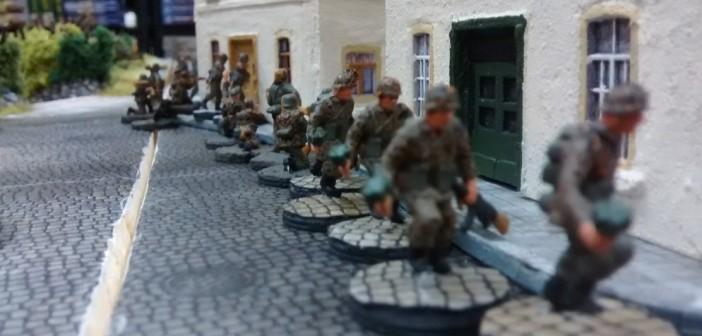 """Auch zum Start-Setting für das Table-Top-System """"Behind-Omaha"""" gehören mehrere 10er-Trupps der deutschen 716. Infanterie-Division, die an der rückwärtigen Stadtgrenze von Saint-Aubin-Sur-Mer marschieren und dem Spieler der deutschen Seite auferlegen, in die Stadt einzumarschieren und diese möglichst nahe am Strand zu verteidigen."""