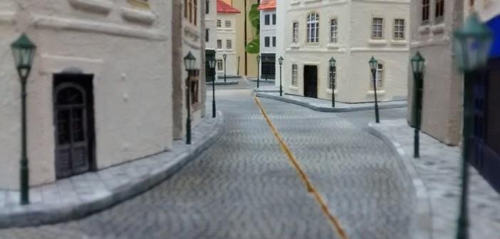 """Lange Sichtachsen sind auf der Dioramenplatte strengstens verpönt. Einzig an den Plattengrenzen sind aus Gründen der Austauschbarkeit Straßen als Schnittstellen angebracht, was - wie man hier sieht - zu einer längeren Sichtachse führt. Im Spiel in Gelnhausen konnte jedoch keine der Spielparteien die quer zur Spielrichtung verlaufenden Sichtachsen an den Schnittstellen nutzen. Von links kommend hier die """"Rue Des Bains"""", die sich rechts fortsetzt und weiter hinten in Bildmitte die """"Rue Bellengers"""", welche rechts aus dem Bild läuft."""