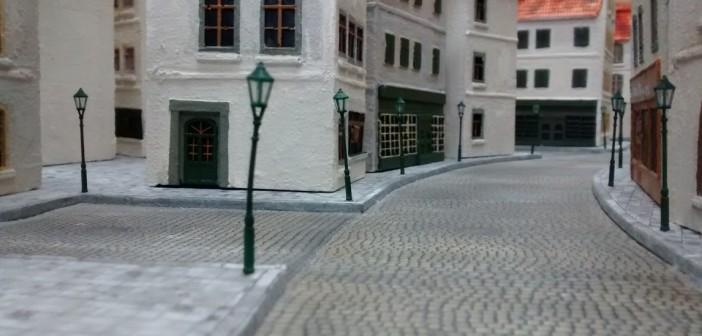 """Der """"Place De La Mairie"""" vor der Bürgermeisterei liegt an der """"Rue Des Bains"""". Der Platz in der Vorstadt lockert das ansonsten französisch eng wirkende Stadtbild von Saint-Aubin-Sur-Mer auf. Im späteren Spiel nutzt der Spieler der deutschen Seite den Platz als Stellung für seine schweren Mörser-Trupps. Weiter hinten sieht man die Einmündung der """"Rue Bellengers"""", die in einem eleganten Bogen zunächst parallel zur """"Rue Des Bains"""" verläuft, bevor sie einmündet."""