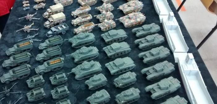 Der Fuhrpark für die beiden Spieler. Churchill und Sherman Firefly sowie Cromwell zur Infanterie-Unterstützung sind dabei. Aufklärungspanzer Stuart, M3 Halbketten und Bren-Carrier für den motorisierten Infanterie-Transport und mehrere 57mm-Paks britischer Herkunft. Die deutsche Seite wartet mit Panzer VI Tiger, Panzer V Panther und mehreren Panzer III und Panzer IV sowie StuG III auf. Der Mannschaftstransport greift hier auf Opel Blitz, Sd.Kfz. 251 sowie Kübelwagen und Schwimmwagen zurück. Kräder und Beiwagenkräder und Pak 40 finden sich ebenfalls. Im ersten Table-Top-Spiel auf der Dioramenplatte in Gelnhausen wurden die Tiger und Panther bevorzugt...