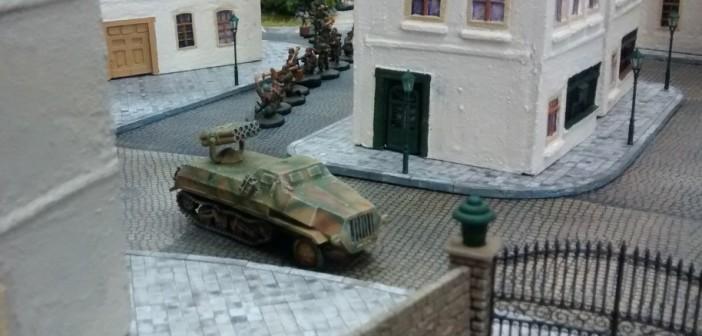 Ein Panzerwerfer 42 biegt in die Straße entlang des Rosengarten ein, gefolgt von einem 10er-Trupp Infanterie. Hier ist das erste Table-Top-Spiel bereits im Gange. Der Spieler der deutschen Seite lässt vorrücken.