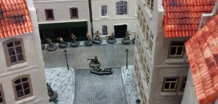 """Abschließend ein Bild einer Spielszene in der Altstadt von Saint-Aubin-Sur-Mer. Von vorne unten kommen die """"Rue Du Tigre"""". Der Vormarsch führt die Spielfiguren des Spielers der alliierten Seite durch die """"Rue Bellengers"""""""