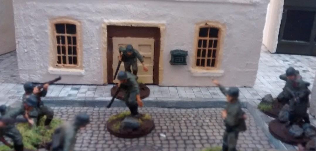 Alarm! Die Invasionsflotte liegt vor der Küste! Aus der Mairie stürmen die Soldaten der 4. Kompanie des Grenadier-Regiments 736 um sich in Richtung Strand in Bewegung zu setzen. Es ist der zweite 10-Mann-Trupp, der in der Stadt das Spiel beginnt.