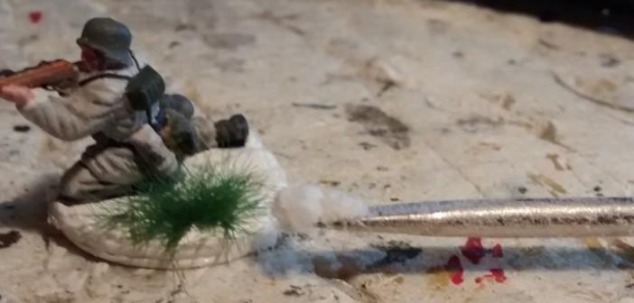 Mit einem kleinen Werkzeug wie einen Spatel oder einem Schraubenzieher wird etwas NOCH Pulverschnee auf das Grasbüschel aufgebracht.
