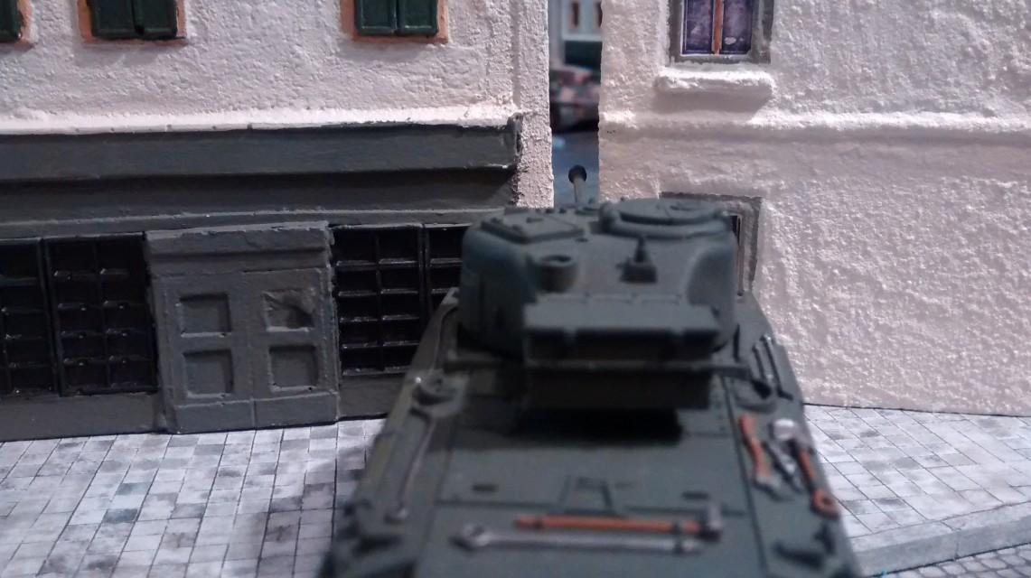 Der Sherman Firefly visiert den Tiger zwischen den Häusern hindurch an.