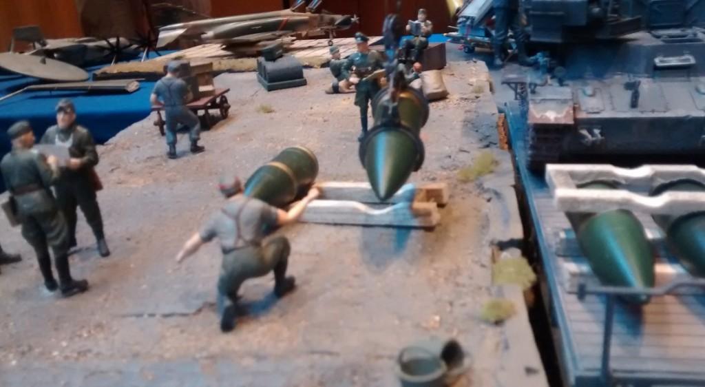Beladeszene an der Laderampe: Mit dem 2,5t-Ladekran hebt der Munitionsschlepper auf Panzer IV Fahrgestell eine 60cm-Granate des Gerät 040 an, um sie auf dem Holzgestell abzulegen. Der Soldat im Vordergrund weist den Kranführer ein. mit seinem 2,5-t-Kran steht auf dem Nachbargleis und verlädt 60cm-Granaten