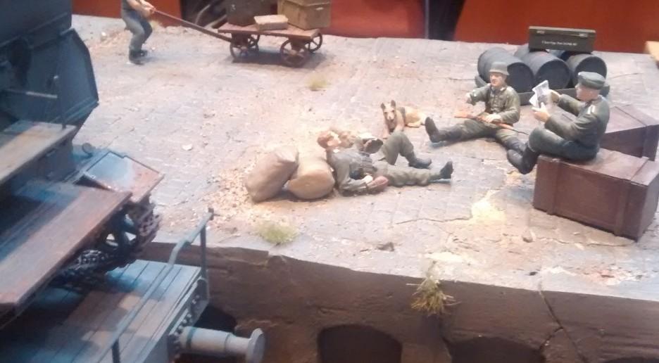 """Beschauliche Szene am Rande der Laderampe: drei Soldaten der bedienmannschaft des gerät 040 Mörser """"Eva"""" bei der Zigarettenpause."""