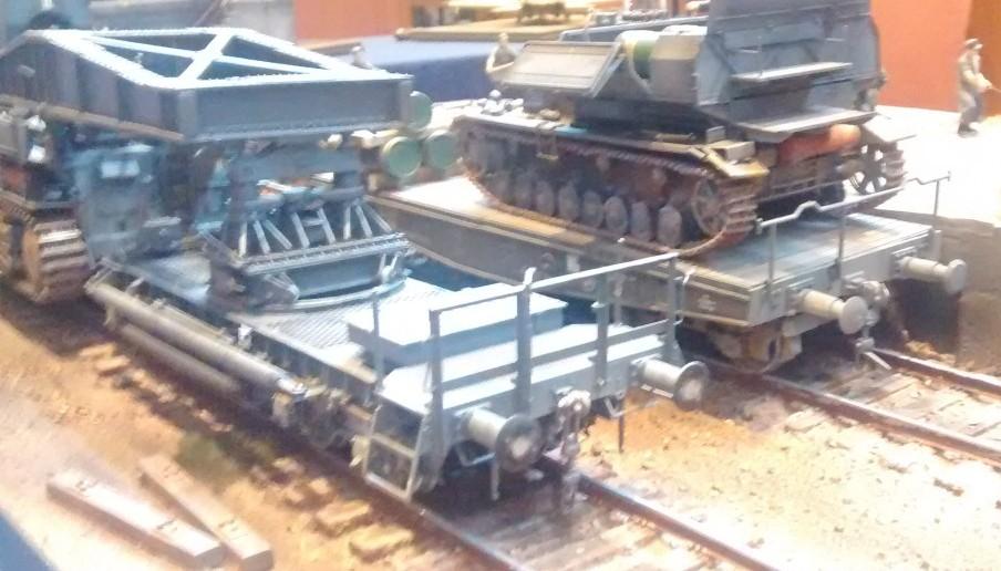 Der Munitionsschlepper auf Panzer IV Fahrgestell mit seinem 2,5-t-Kran steht auf dem Nachbargleis und verlädt 60cm-Granaten