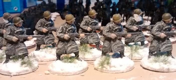Hier die 8 GIs für die 99th Infantry Division. Die Bases wurden mit weißer Farbe überzogen, dann mit Modellbahnschnee bestreut. Ein paar eingeschneite Grasbüschels von MiniNatur kamen auch noch mit drauf.