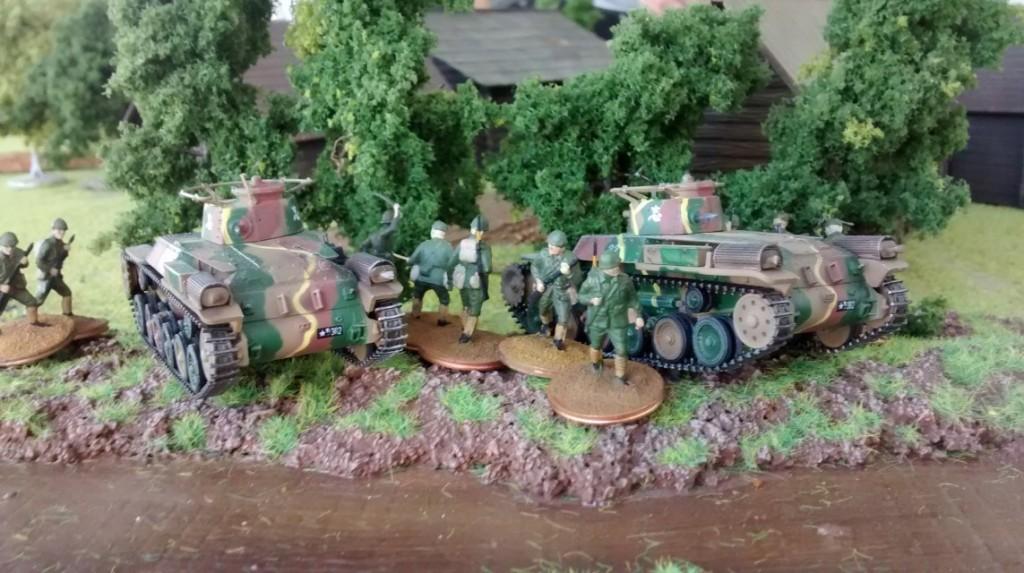 Zwei leichte japanische Kampfpanzer Type 95 Chi-Ha gehen hinter einem Wäldchen in Stellung.