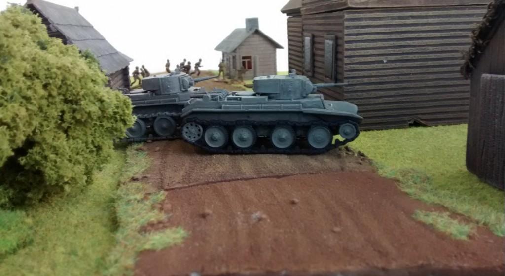 Die schnellen BT-7 stoßen mit begleitender Infanterie über die Dorfstraße vor.