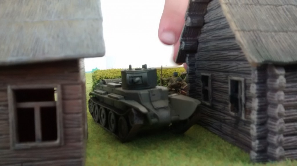 Ein leichter Panzer BT-7 ist zwischen zwei Bauernkaten in Deckung gegangen.
