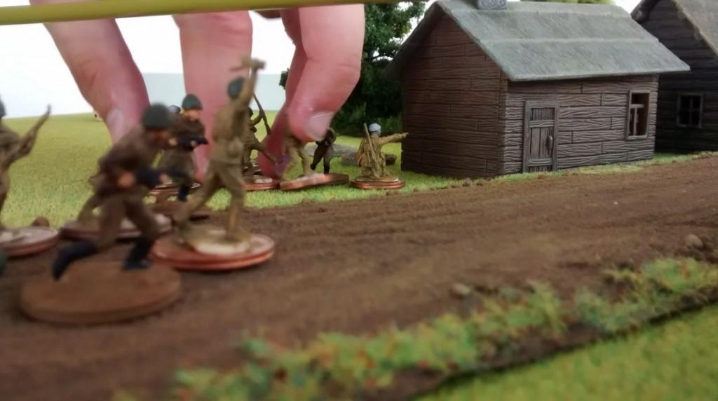 Russische Infanterie stößt entlang der Dorfstraße vor.