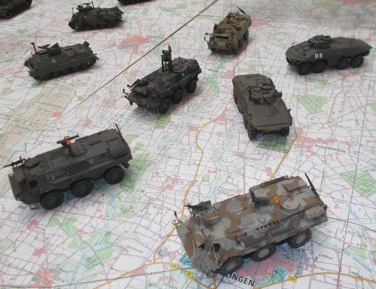 Bundeswehrfahrzeuge auf topographischen Karten inszeniert.