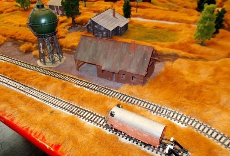 Eine der Behind Omaha Spielplatten. Hier der schmucke Bahnhof mit den Märklin HO-Gleisen. Auch die anderen 1:87-Häuser von der Modellbahn fügen sich stimmungsvoll in das Landschaftsbild ein.