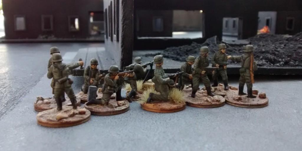 Der andere 10er-Trupp hat mittlerweile die kritische Straße ohne Verluste überquert. Hinter der Ruine geht er erstmal in Deckung. Nur kein Aufsehen erregen!