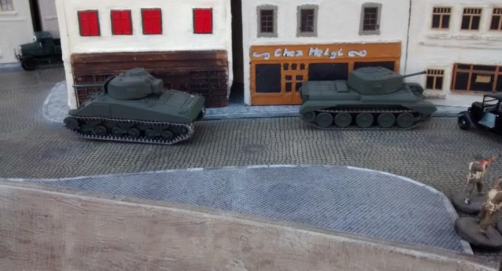 Cromwell und Schörmi ziehen noch nicht vor und verharren in der Deckung der Stadthäuser an der Strandpromenade. Ohne die Deckung durch die begleitende Infanterie will der kanadische Spieler seine beiden wertvollen Tanks nicht den deutschen Nahkämpfern und Panzerschreckschützen des deutschen Spielers aussetzen.