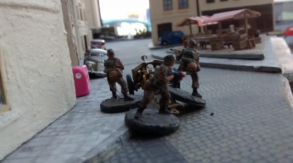 Die drei verbliebenen Schützen des Leutnant Schuster verbleiben hinter ihrer Pak 40 in Stellung. Die kann die ganze Straße bestreichen.