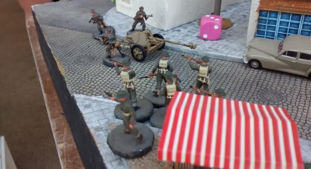 Sergeant Chippi sprintet um den Place du marché zur Stellung der Pak 40. Er geht die Bedienmannschaft direkt an. Er hofft, das Geschütz in Besitz nehmen zu können...