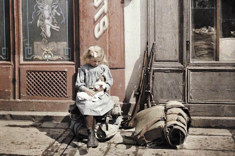 Ein kleines Mädchen spielt mit seiner Puppe - während es neben zwei Gewehren und einem Militärrucksack sitzt. Eine Straße in Reims.