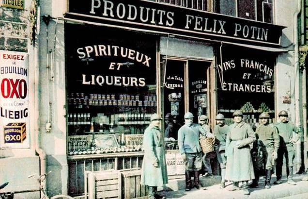 Französische Soldaten posen vor einem Laden mit Wein und Spirituosen in Reims