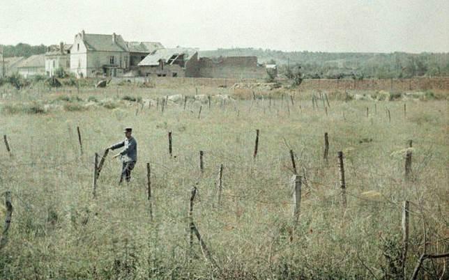 Ein Offizier prüft einen Stacheldrahtverhau bei Soissons