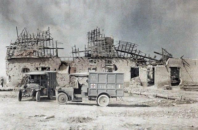 Zwei Ambulanzfahrzeuge vor einem Haus nahe der Ortschaft Boezinge im Norden von Ypern in Belgien, das durch Artilleriefeuer verwüstet wurde.
