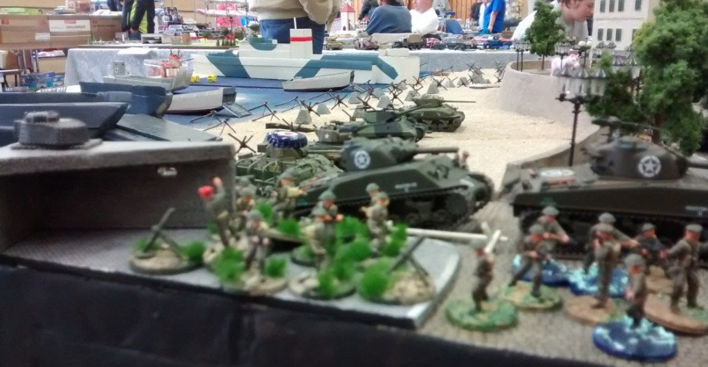 Am Strand sind noch weitere Tanks und Jagdpanzer aufgefahren, die auf ihren Einsatz warten. Ein Glück, dass die deutsche Küstenbatterie im Hinterland keinen vorgeschobenen Artilleriebeobachter in Strandnähe im Einsatz hat.