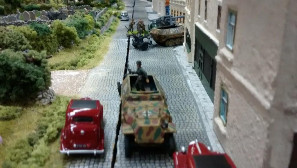 """Auf der Schnellstraße am Ortsrand von Saint-Aubin-Sur-Mer haben die beiden deutschen Spieler ihre Aufstellungszone. Im Hintergrund sieht man eine Acht-Acht-Flak, die an der Hauptstraße stadteinwärts in Stellung gegangen ist. """"Hier kommt keiner durch!"""" wird als Parole ausgegeben. Die 251er verschuben noch rasch einige 10er-Trupps Panzergrenadiere."""