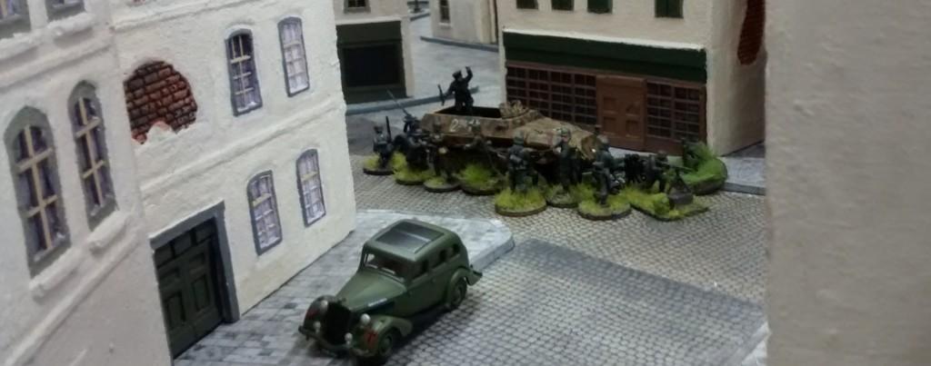 Auf der Ausfallstraße in Nähe der Stadtmitte sitzt ein 10er-Trupp ab. Auch diese Herrschaften führen einen schweren Granatwerfer mit sich.