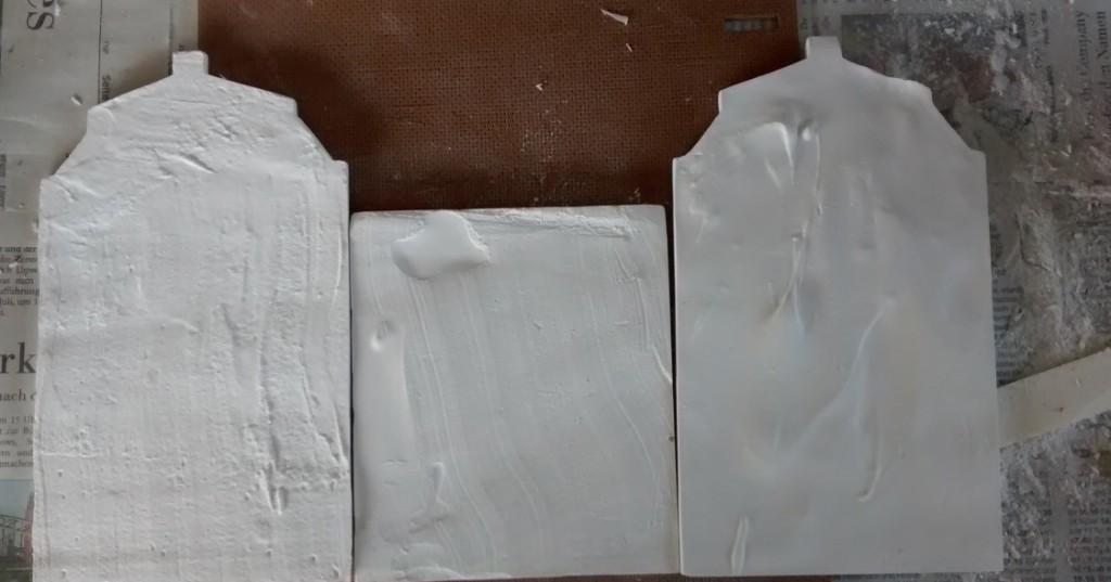 """Schritt 1: die Fassadenteile des zu montierenden Hauses werden """"auseinandergefaltet"""" abgelegt. Die zu beklebenden Seiten (Innenseiten) zeigen nun nach oben."""
