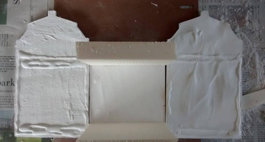 Schritt 2: die Stabilisierungsplatten werden auf die mit Ponal bestrichenen Stellen auf der mittleren Fassadenplatte aufgesetzt. Auch an den seitlichen Fassadenteilen kann man bereits den Bestrich mit Ponal erkennen.