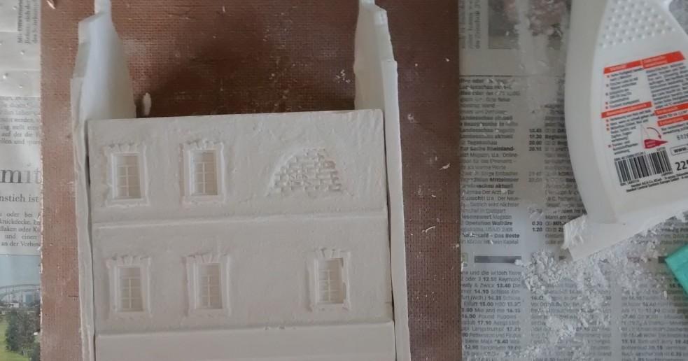 Schritt 3: durch Beiklappen und Festkleben der Seiten-Fassadenteile entsteht schnell das Haus. Im vierten Schritt wird die vierte Fassade oben aufgeklebt.