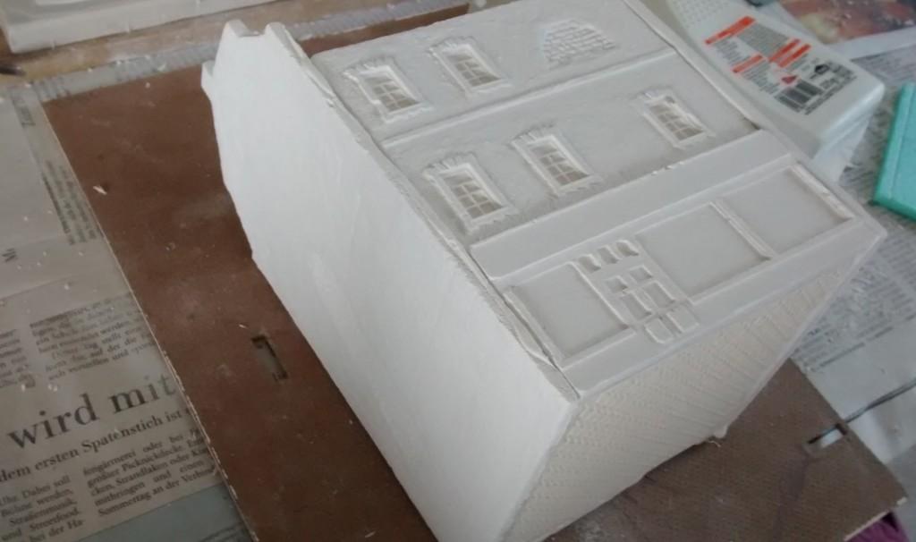 Hier kann man sehen, wie die untere Stabilisierungsplatte die Bodenplatte des Hauses bildet. Später habe ich zum Unterstützen des Abbindevorgangs noch Einmachgummis um die Fassadenteile geschlungen. So wurden die Fassadenteile noch fester aneinander gepresst.