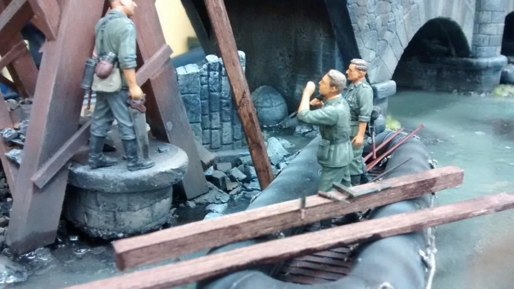 Drei Pioniere des Pionier-Bataillon 45 beim Brückenbau. Die Säge in der Hand des eine Pioniers verkündet schwere Knochenarbeit. Schöne Details: ddie auf dem balken liegenden Werkzeuge.