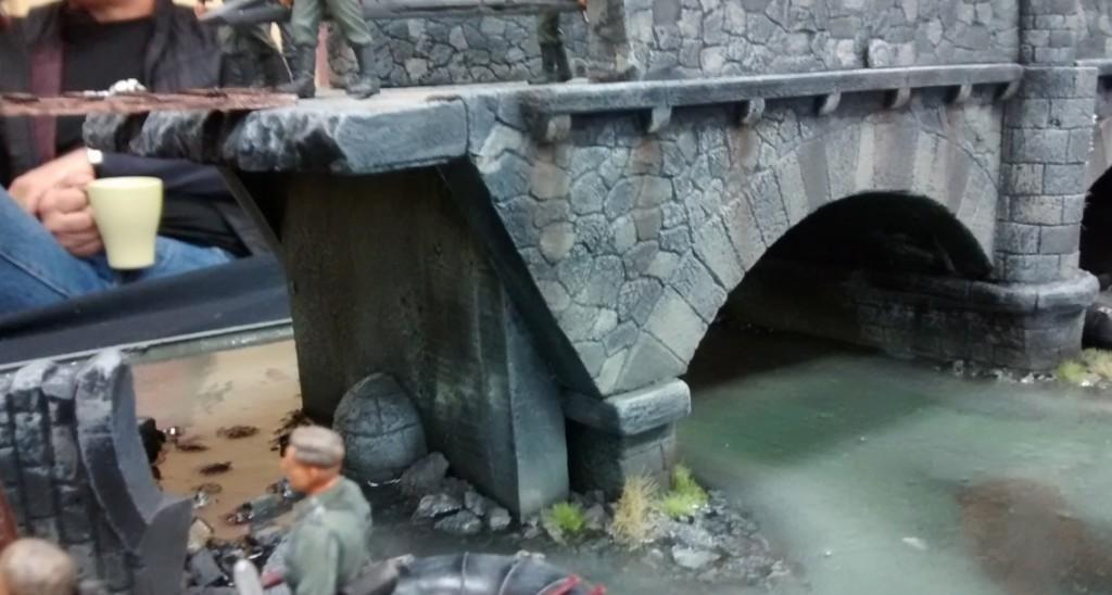 Man beachte die detailreich gestaltete Brücke und das oberecht wirkende Wasser des Flusses.