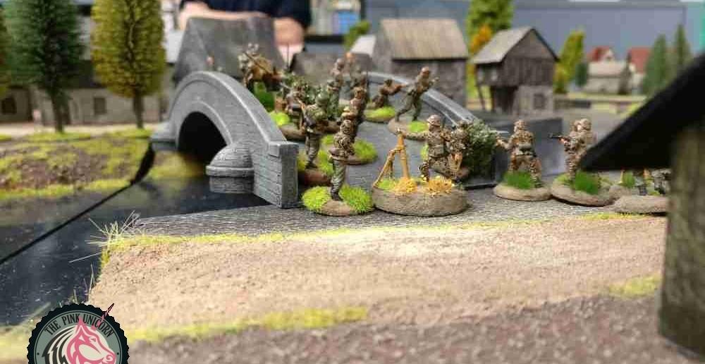 Am Dorf hat die Infanterie mit ihren beiden 10er-Trupps mit schweren 81mm-Granatwerfern die Steinbrücke erreicht. Es bleibt abzuwarten, ob die beiden 10er-Trupps den zur Plattenmitte hingewandten Ortsausgang rechtzeitig werden erreichen können, um die 251/9er zu unterstützen. Die Briten haben einen kürzeren Anmarschweg und sind wesentlich schneller ans die deutschen Grenadiere. ( Behind Omaha. Forum / Spielbericht )