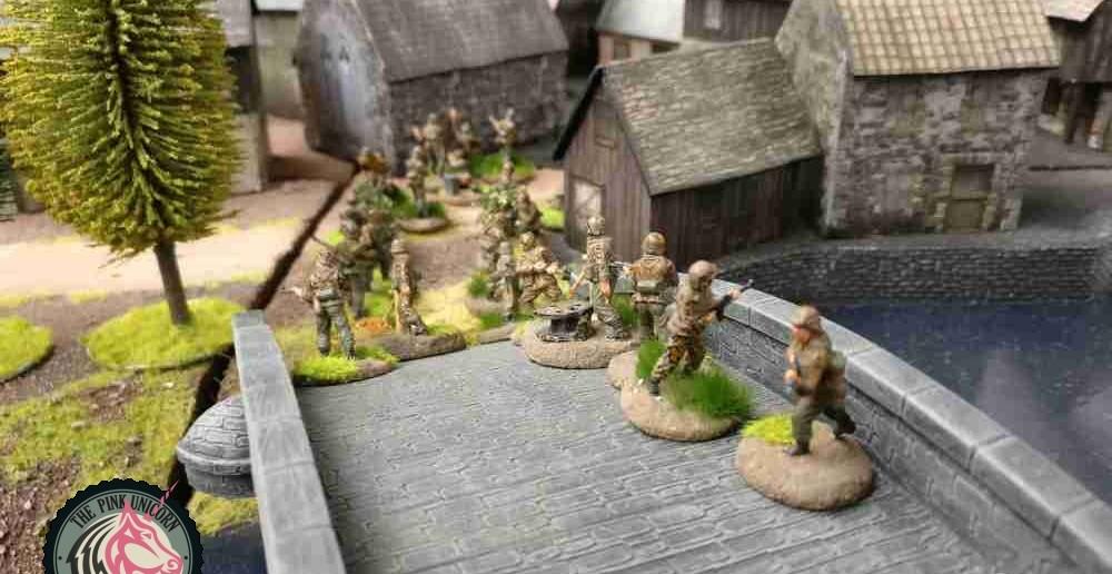 Die deutschen Grenadiere rücken ins Dorf ein. Der Feind steht bereits am anderen Ortsausgang. Insofern kommt man etwas zu spät, um sofort den kampf aufnehmen zu können. Hier sind die deutschen Truppen im Nachteil. Die beiden Sd.Kfz. 251/9 sind wesentlich schwächer als die drei britischen Kontrahenten. ( Behind Omaha. Forum / Spielbericht )