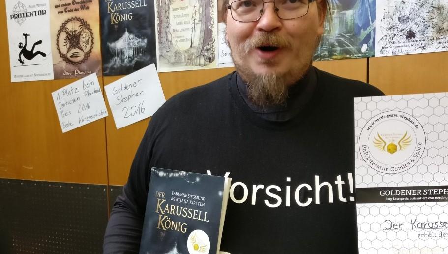 """Stolz hält Torsten Low die Urkunde des Goldeneen Stephan 2016 ( Kategoeie """"Roman"""" ) und sein Buch """"Der Karusellkönig"""" hoch, für das er den Preis abgeräumt hat."""