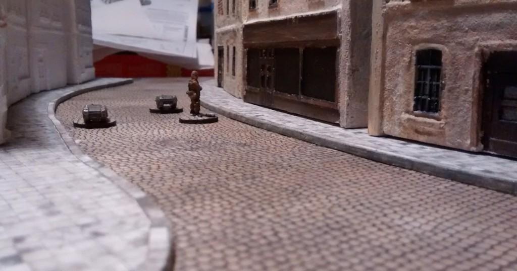Hier die ersten probegestellten Häuser in einer der beiden Längsstraßen der Normandie-Dioramenplatte. Man erkennt jetzt schon, dass die Häuser der Straße eine gefällige Kurve bilden. An der Figur und den beiden Goliaths erkennt man auch, dass in der Straße hinreichend Bewegungsfreiheit für das Spiel besteht. Für unsere geplanten Spiele in der Normandie ist ohnehin viel Infanteriespiel vorgesehen.