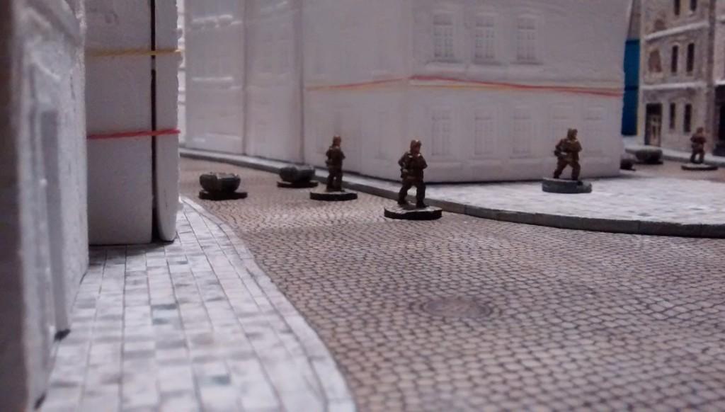 """Zu dem großen freien Platz hin, weitet sich die Spielplatte angenehm auf. Der freie Platz auf dem Gehsteig wird später noch von einem MG-Bunker belegt. In der Normandie waren unzählige dieser kleinen """"Pillboxes""""  verbaut."""