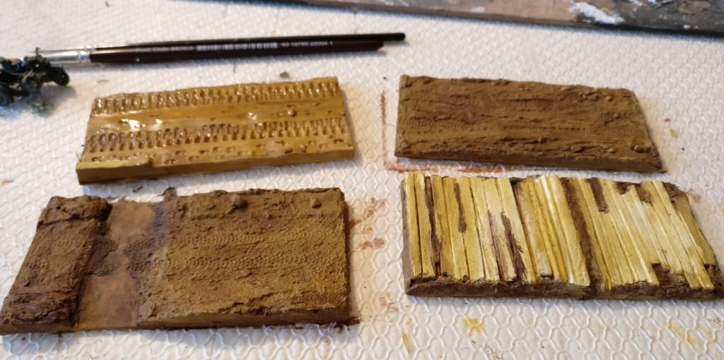 Der Auftrag der Lasur mit der Farbe REVELL Aquacolor 361 84 Lederbraun erfolgt unterschiedliche kräftig. Bei der als regennasse Trasse geplanten Base wird nur sehr wenig Farbpigment aufgetragen, während die Bases der Feldwege kräftiger eingefärbt werden. Der Knüppeldamm wird ebenfalls weniger intensiv bemalt, da er helle Holzbalken aufweisen soll.