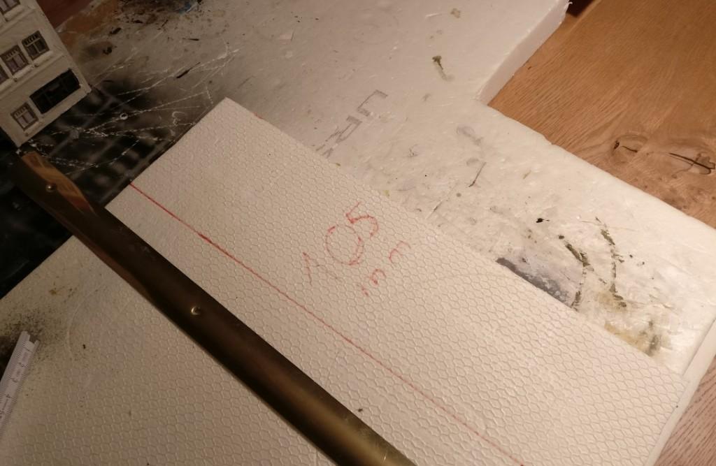 Hier messe ich von der verbliebenen 20mm-Styrodurplatte den 105mm breiten Streifen für die breiteren Häuser ab.