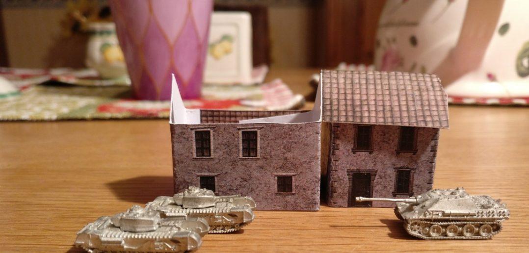 Zwo Churchill und ein Jagdpanther geben sich ein Stelldichein vor zwei  Papierhäusern im Maßstab 1:285 (6mm) von Doncolor.