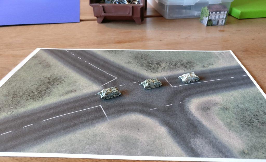 Drei SU-122 auf einer Straßenkreuzung. Die Spielplatte hat die Größe DIN A4. Maßstab 6mm / 1:285.
